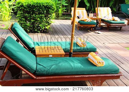 Cozy daybed with umbrellas by the pool