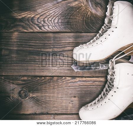 a pair of white leather skates hanging on a brown wooden wall