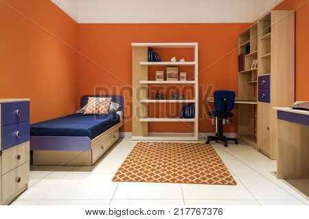 Shot of a modern colorful children's room. Room for the teenager with a small bed with blue linens. In the room, wardrobes, tables, computer Desk
