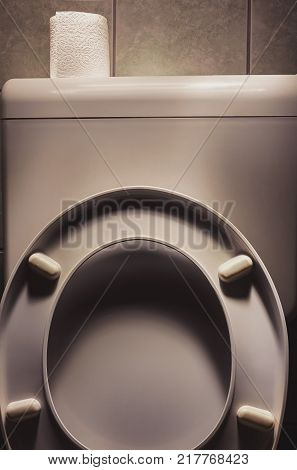 Old used toilet with toilet paper on top accentuated objects with light.