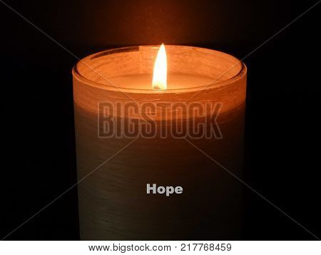 A burning candle against a black background with the word