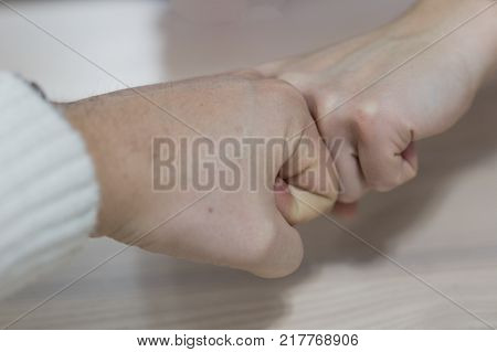 Fist to fist. Male vs female hand.