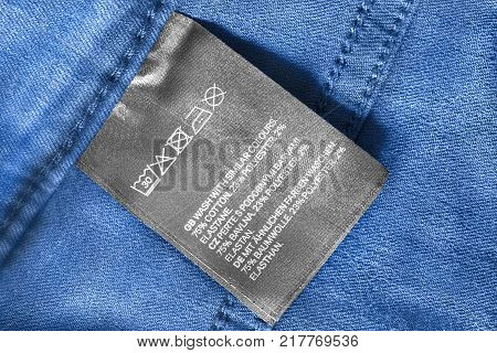 Fabric composition and washing instructions clothes label on blue denim background