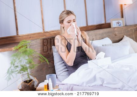 Feeling unwell. Ill young woman having a running nose while lying in bed at home