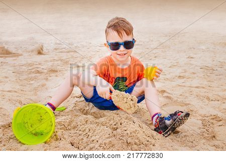 A boy on the beach playing with sand. A child is playing on the beach. Pail and spatula.
