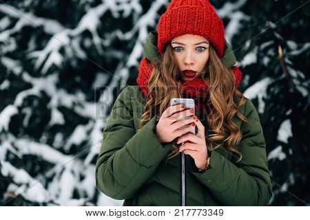 Surprised Girl Stares At Smartphone In Winter Day.