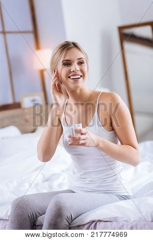In upbeat mood. Pleasant pretty woman sitting on the edge of her bed, holding a cup of coffee and touching her face