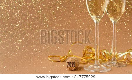 Champagne flutes and bottle cork with 2019 numbers at golden holiday background with glitters and tinsel. Celebrating christmas, new year or birthday. Mockup for xmas postcard, crop