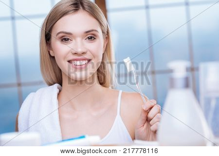 Love hygiene. Beautiful upbeat woman showing her transparent toothbrush and smiling at the camera while carrying a towel on her shoulder