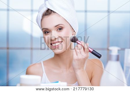 Natural makeup. Upbeat young woman applying some powder to her skin while smiling brightly and wearing a towel turban