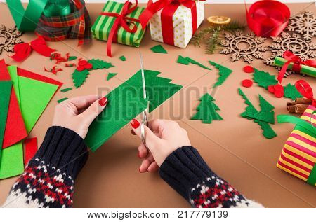 Creative diy craft hobby. Woman makes felt Christmas tree decoration on table with felt sheets and scraps, scissors and trappings. Closeup of female hands at craft paper background.