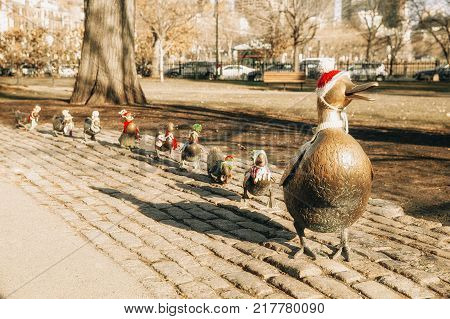BOSTON MA, USA - December 7, 2017:  famous ducklings in Christmas hats. statue Make Way For Ducklings at Boston Public Garden