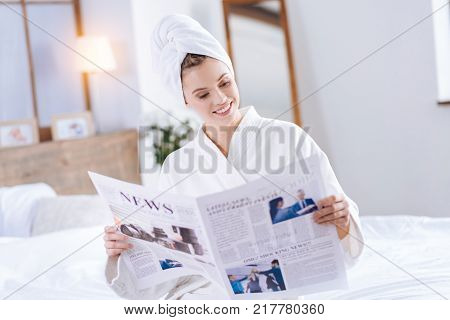 Breaking news. Pleasant pretty woman in towel turban and a bathrobe sitting on the bed and reading articles in the newspaper