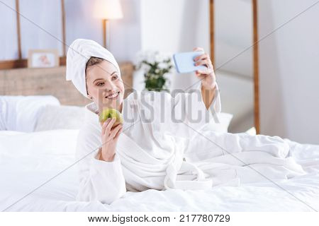Healthy breakfast. Upbeat young woman lying on the bed, holding an apple and taking a selfie with it while wearing a towel turban and a bathrobe