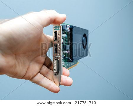 Man holding against gray background powerful GPU video card used in professional video production in bitcoin cryptocurrency mining