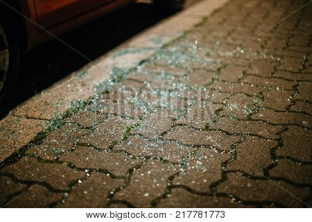 Shattered glass in myriads of pieces seen on the street near the parked car at night - thief traces or accident