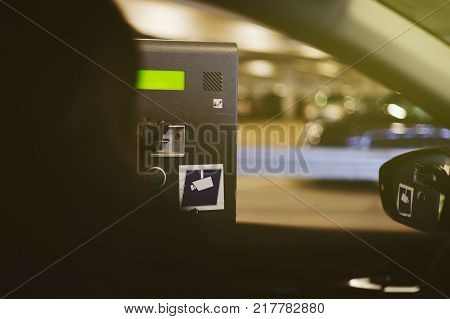 Woman taking parking meter ticket slip from the automated distribution machine gate