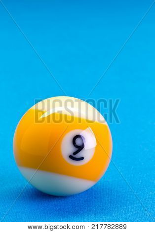 Billiard pool game nine ball on billiard table with blue cloth copy space