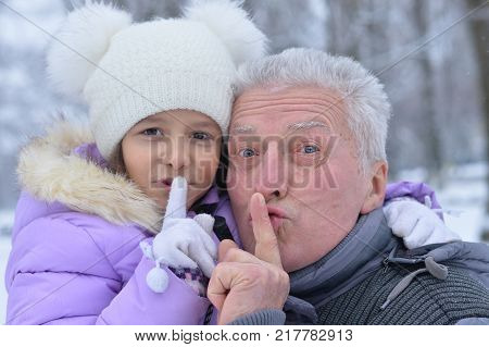 grandfather with granddaughter call for silence , posing outdoors in winter poster