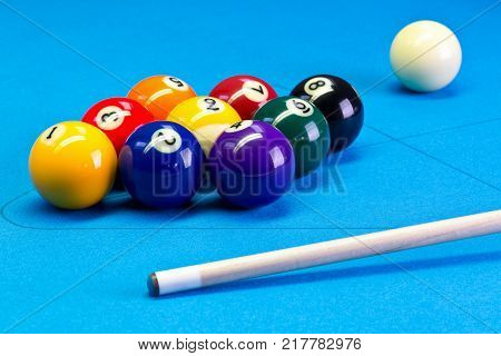 Billiard pool game nine ball with nineball balls set up with cue on billiard table with blue cloth