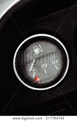 Classic pointer indicator of fuel level of the car. Low gasoline level with red alarm light lamp. Empty fuel tank.