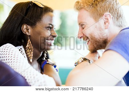 Romantic couple smiling while looking into each others eyes with love