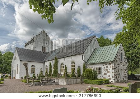 Parishioners leaving the old white norra vrams church in the swedish village of Billesholm.