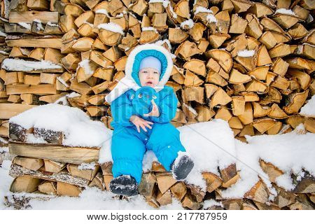 Baby boy sitting on a stack of firewood with a winter snow