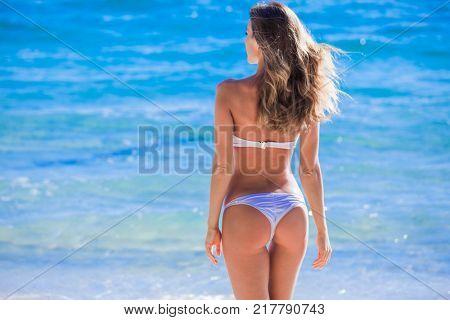 Woman with perfect body in bikini over blue sea background