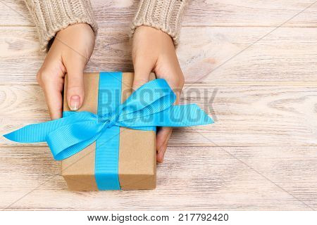 Girl tying a simple blue bow on a gift box. Wrapped in plain craft paper and Blue ribbon. Finishing touches.