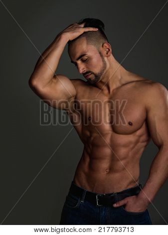 Dieting and fitness. Sport and workout. Athletic bodybuilder man on grey background. Man with muscular body and torso. Coach sportsman with bare chest in jeans.