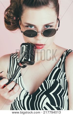 Girl in glasses sing in microphone. Pin up young girl on pink background radio. Music look and retro style pinup. Beauty and vintage fashion. Woman singer with stylish retro hair and makeup.