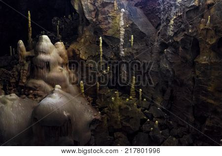 cave with colourful textured walls and stalactites and stalagmite lit from behind