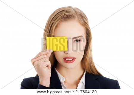 Beautiful caucasian business woman holding yellow empty personal card.