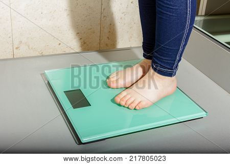 Child's foot is standing on modern floor scale measuring her weight.