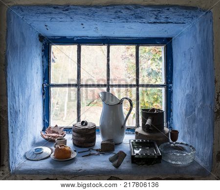 Nostalgic autumn country windowsill still life with various old objects framed by blue walls poster