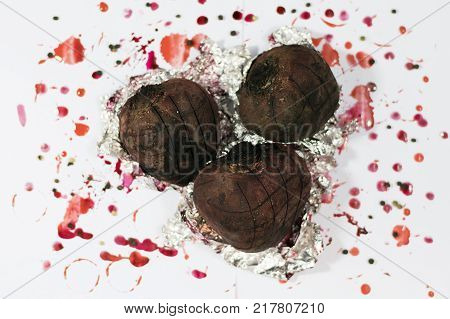 Baking with aluminium foil. Baked beets for a Christmas soup. Holiday food. Top view beets on a white background with stains