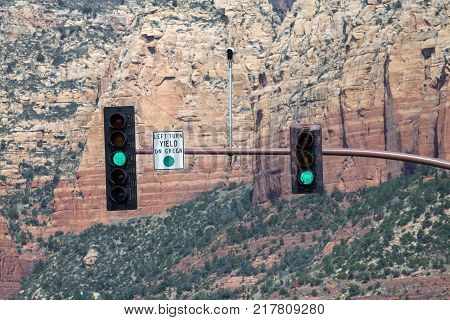 A traffic light and regulatory sign with a mountain in the background in Arizona