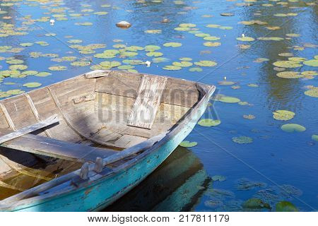 Old wooden rowboat painted in wethered green color tied up. Water lilys on the water