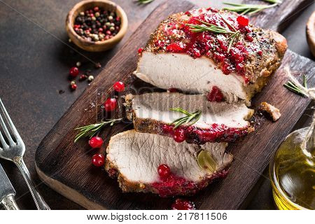 Pork ham baked in the oven with cranberry sauce. Winter meat recipe.