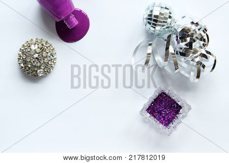 Ultra violet nail polish spills with glitter, jewelry and silver decorations. Copy space.