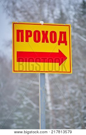 Yellow direction sign with red word and arrow on winter forest background on vertical shot