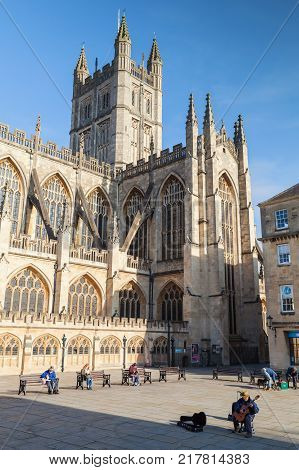 Bath United Kingdom - November 2 2017: Street view with The Abbey Church of Saint Peter and Saint Paul Bath commonly known as Bath Abbey. Street musician plays on guitar