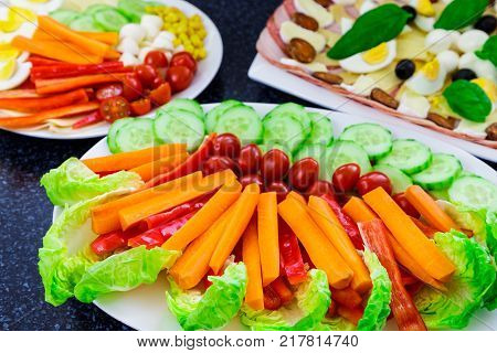 Buffet catering food with basil egg mozarella sausage ham olive carrot tomatoes and others vegatables arangement on table.