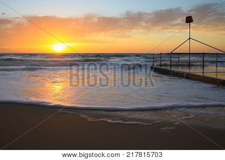 Holiday daybreak sunrise over coastal ocean water with beach and jetty landscape. Orange sky.