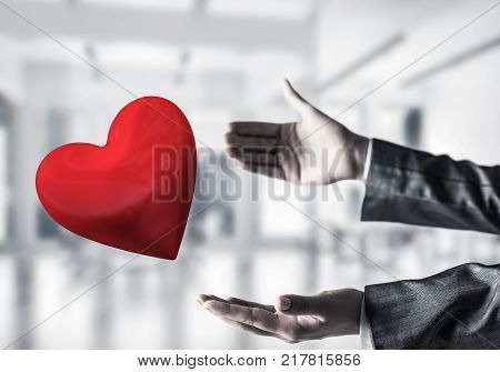 Cropped image of business woman in suit keeping big red heart in his hands with office view and sunlight on background. Mixed media.