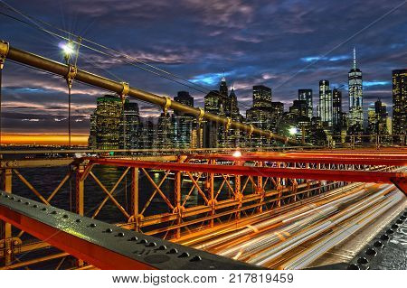 View of sunset over a Lower Manhattan from Brooklyn Bridge.