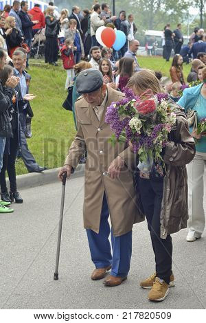 PYATIGORSK, RUSSIA - MAY 09, 2017: Young carer and elderly man with a walking stick on Victory Day on a parade of 9 may