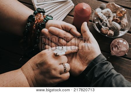 Witch or fortune teller reading fortune lines on male palm or hand, mystic esoteric or medium paranormal chiromancy or palmistry concept, toned