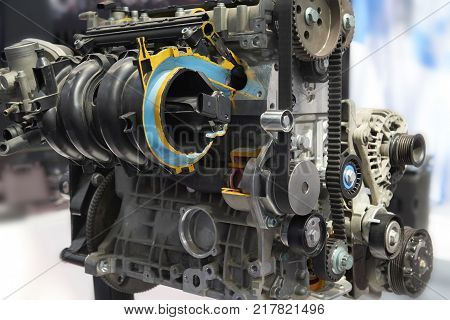 Front view on clean car engine toothed belt, pulley, electric equipment, engine components. Engine with cross section. Close up car motor components details parts. Car motor repair works. MOT